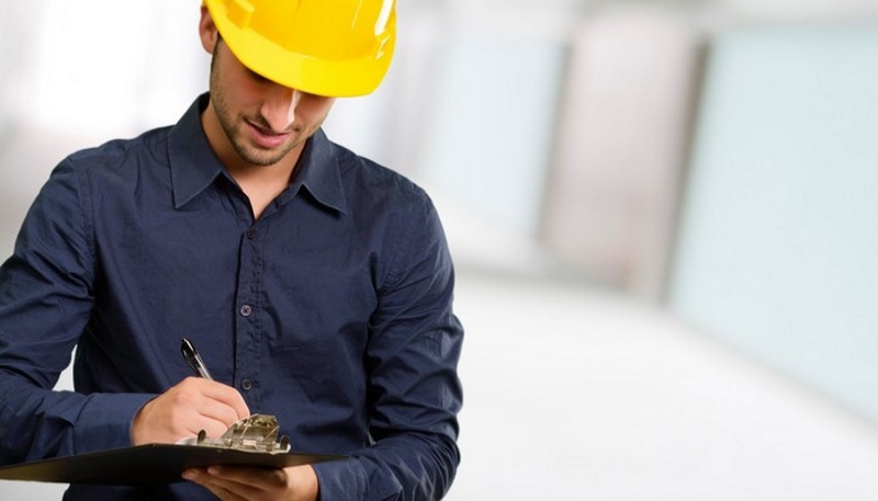 Man with hardhat using clipboard that could be a checklist